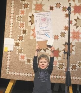 """Children were a big part of the Fairlawn Auxiliary Auction, Friday, April 8, with a preview the night before. Top left: Isaac Nafziger, 4, holds up a sign announcing the whole hog and processing that were put up for auction, which sold for $500. Behind him is this year's feature quilt, titled """"Wedding Bands,"""" which sold for $1,600. The quilt was completed in 27 weeks by women from 11 churches, volunteering 378 hours in quilting. It was pieced by Gwen Kruse, marked by CaraLou Grieser, and bound by Suzie Schrock. Top right: While Bob Frey, auctioneer, drums up bids, Leah Roth, 8, Pettisville, holds a wall hanging. Bottom left: Oliver Nafziger, 18 months, rides the rocking motorcycle that sold for $130. Bottom right: The Fairlawn commemorative plate, crafted by Mark Nafziger, potter at Sauder Village. It sold for $250.– photos by David Pugh and Mary Huber"""