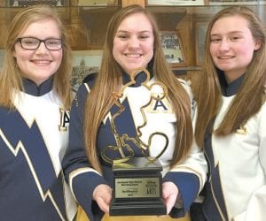Darby Stevens, Emily Rose, and Kenzie Short, AHS marching band field commanders, from left, hold the Disney Performing Arts trophy for participation the band received for marching in the Magic Kingdom parade. While they had fun on the trip to Disney World in Florida over spring break, band members said they learned lessons about music and life.– courtesy photo