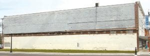 The south-facing wall of the Rupp Furniture building as it appeared Tuesday, April 19. The lower level served as the inside wall of the Red Cross Drug Store; the brick section is where the Red Cross ceiling tied into the Rupp building wall. The area above has always been exposed. By July 1, a contractor will refinish the entire wall space.– photo by David Pugh