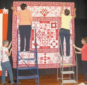 """These women were among several persons who were busy Monday, April 25, preparing the 2016 Sauder Village Quilt Show. From left: Bonnie Stuckey, West Unity; Suzie Rupp, rural Stryker; Linda Stuckey, Archbold, and Karen Short, rural Archbold. The quilt is one of several of a special exhibit, """"A Ruby Red Celebration,"""" in honor of the 40th anniversary of the quilt show.– photo by David Pugh"""
