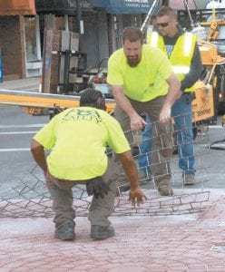 Workers from A&A Safety, Amelia, imprint another portion of pavement at the intersection of North Defiance Street and Holland Street Tuesday.– photos by Mary Huber