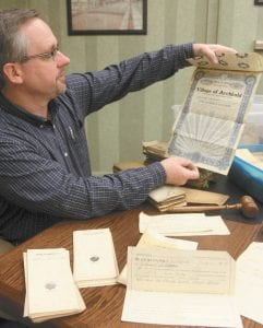"""Top left: Jim Wyse, who was the mayor of Archbold in 2012, looks over some of the contents of a box of old village records. The box was found in a corner of a storage room at the Archbold municipal building. It contained documents like this $500 """"Defiance Street Improvement Bond"""" from 1911. Some documents date back to 1896. Top right: Tracie Evans, curator of collections at Sauder Village, with some records she restored for German Township. After a July 1, 2012 windstorm damaged the township building, Sauder Village held onto the documents, then later began a restoration project. Bottom right: a ticket to the 1916 Fulton County Fair, one of thousands of items found in the treasure trove of old papers."""