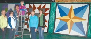 Many women spent long hours painting giant quilt blocks on eight-foot squares made of wood. They are placed on barns throughout the Archbold Area School District to become a barn quilt trail for the Sesquicentennial. From left: Sabrina Grisier, Linda Rufenacht, Nancy Vershum, Bonnie Stuckey, Nancy Ruffer and Diane Tinsman. Not pictured: Sue Hurst, Heidi Miller.– photo by David Pugh