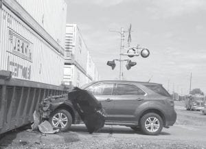 The driver of this sport-utility vehicle was not injured after it was struck by a train at the Co. Rd. D slant crossing. Note that while the front of the vehicle suffered heavy damage, the passenger compartment remains intact. – photo by David Pugh