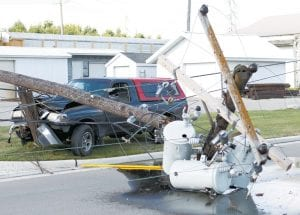 Three electrical transformers lay on the ground, and at least one is leaking a mineral-oil based substance, following an accident, Sunday, Aug. 13. The pickup in the photo struck the utility pole, which brought down the transformers and damaged a second pole.– photo by Mary Huber