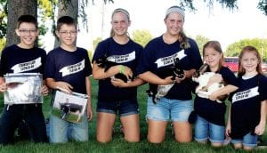 There are three sets of twins in the Countryside Clovers 4-H club. From left: Wyatt and Dakota Armstrong, 12; Kacie and Gracie Wolf, 13, and Katelyn and Kendall Liechty, 7, all of rural Archbold. Wyatt and Dakota will each show a cow at the Fulton County Fair; Kacie and Gracie will show rabbits. While Katelyn Liechty holds a rabbit, the seven-year-olds won't have animals at the fair.– photo by David Pugh