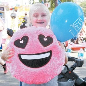 Taylor Wachtmann, 6, Wauseon, shows off her prize from winning the balloon dart game. Her teeth are blue from eating Italian ice. She is the daughter of John and Jessica (Sauder) Wachtmann.– photo by Mary Huber