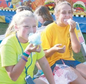 Nyah Grime, 11, left, and Kaylen Behnfeldt, 11, both of Archbold, take a couple of bites out of their cotton candy.– photo by Mary Huber