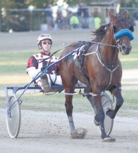 First Official, with Mark Headworth as the jockey, runs in one of the harness races at the fair. Denny Miller, Archbold, is an owner of the horse.– photo by Mary Huber