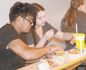 The Pettisville Music Boosters stand is always a popular place to grab a bite to eat. Left: Benny Gomez, 19, Archbold, and Bobbi Kennedy, 18, Wauseon, enjoy burgers and french fries. Right: Carrie Nafziger, right, chats with her husband Randy, and son, Zac, 12, after they enjoyed some fair food.– photo by Mary Huber