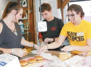 Autumn Ryan, Evan Warner, and Zoe Bullano, from left, help prepare sausage sandwiches at the Fulton County Pork Producers stand. Ryan and Warner are Pettisville seniors, while Bullano is a PHS sophomore.– photo by Mary Huber