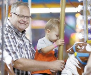 Pat Wyse, Archbold, holds grandson Dalton Wyse, 20 months, Wauseon, on the merry-go-round.– photo by Mary Huber