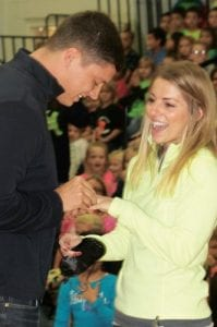 Bzovi slides an engagement ring onto the finger of Wills in front of hundreds of Archbold Elementary Students.– photo by David Pugh