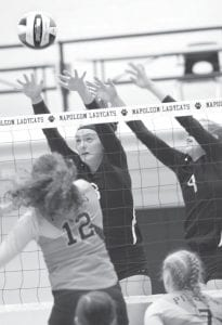 Jess Youse and Morgan Leppelmeier (9) go up to block Ayersville's Logan Tijerina in a Div. IV district semifinal, Tuesday, Oct. 24, at Napoleon.– photo by Mary Huber