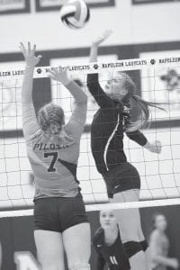 Morgan Leppelmeier taps the ball over Ayersville's Kryshel Dales (7).– photo by Mary Huber