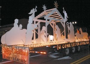 Amy Krueger, executive director of the Archbold Area Chamber of Commerce, announced the winning floats in the Archbold Parade of Lights, Friday, Nov. 24. Top: Clancy's Cabinets was selected as the first-place winner. Middle: Sauder Manufacturing had the second-place winner. Bottom: The Country Dog Salon received the third-place award.– photos by Mary Huber and David Pugh