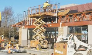A worker on a scissors lift begins installing the framework for the new exterior of the Archbold McDonald's.– photo by David Pugh