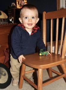Tucker James Trowbridge, the Archbold Buckeye First Baby of 2017, with a toy tractor at his home in rural Archbold. As a farm boy, he's already ridden on farm equipment, including a tractor and a combine. He's logged an estimated 4,000 miles in the pickup traveling to hog shows. His first birthday will be Tuesday, Jan. 2, 2018.– photo by David Pugh