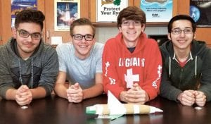 """Trea Ponce, Noah Powers, Connor Hagans, and Mario Estrada, AHS seniors, from left, won an engineering competition involving rockets powered by air pressure. Their rocket, """"The Baked Potato,"""" in the foreground, was not the best-appearing rocket in the competition, but flew well enough to win.– photo by David Pugh"""