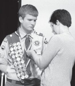 Beth Baus, Archbold, pins the Eagle Scout medal on her son Levi, 15, during a Court of Honor ceremony, Saturday, Feb. 10. His Eagle Scout service project won a Service Project of the Year award, and moves forward in regional, and possibly national, competition.– photo by David Pugh
