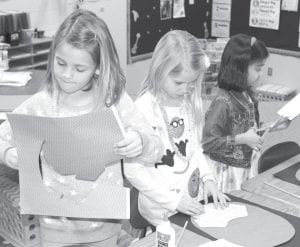 From left, Liza Rufenacht, Demi Short, and Naomi Francis concentrate on one of the many activities students participated in during the 100 Day celebration at Archbold Elementary School, Friday, Feb. 16. The girls are working on pictures of themselves, as they believe they would look in 100 years. The annual 100 Day event celebrates the 100th day of school.– photo by David Pugh